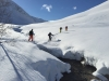 Ski touring and crossing a river in the Lyngen Alps